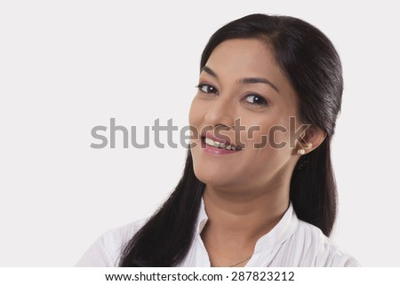 Portrait of mid adult woman smiling over white background