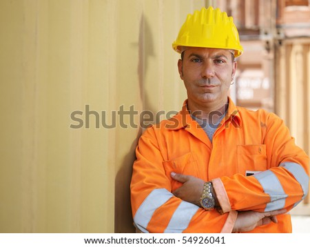 portrait of mid adult worker leaning on cargo container and looking at camera. Horizontal shape, front view, copy space - stock photo