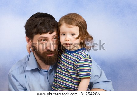 Portrait of mid-aged Jew wearing skullcap and hugging two years old baby boy - stock photo