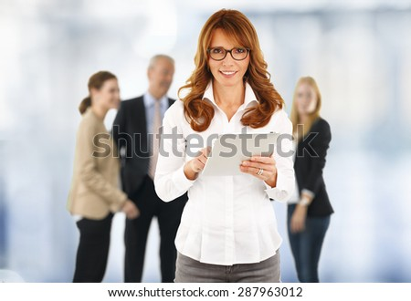 Portrait of middle age businesswoman holding digital tablet in her hand and touch screen while looking at camera and smiling.  - stock photo