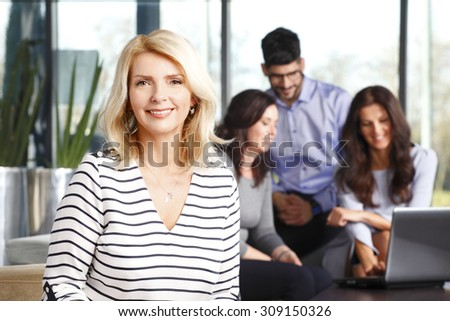 Portrait of middle age businesswoman sitting at office and smiling while sales team working at background on the new project.