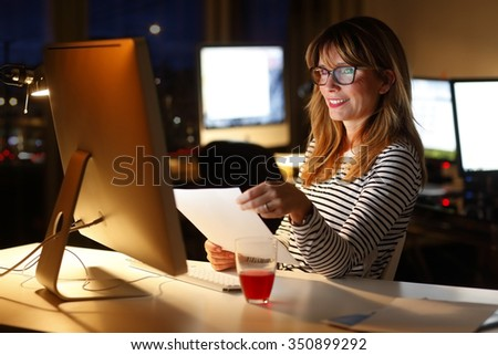 Portrait of middle age businesswoman sitting at office desk and working late in front of computer. Casual professional officer holding in her hands a document and analyzing financial data.