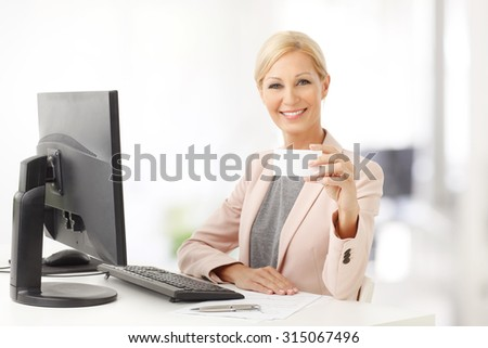 Portrait of middle age businesswoman sitting at office in front of computer and working while showing his blank business card.