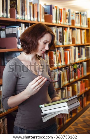 Portrait of middle age mature brunette Caucasian woman student with glasses in library holding book, looking away from camera, teacher librarian profession, back to school concept - stock photo