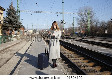 Portrait of middle age professional woman using digital tablet and checking timetable while standing at train station. - stock photo