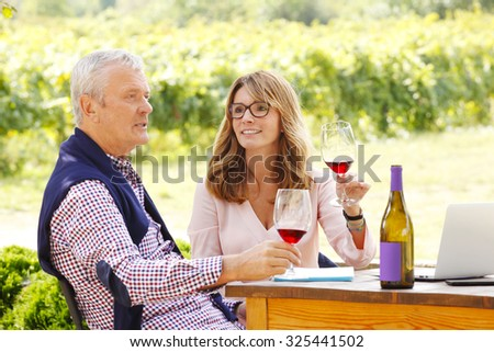 Portrait of middle age winemaker woman holding in her hand a glass of red wine and consulting with senior sommelier while sitting in front of laptop at family winery. Small business.