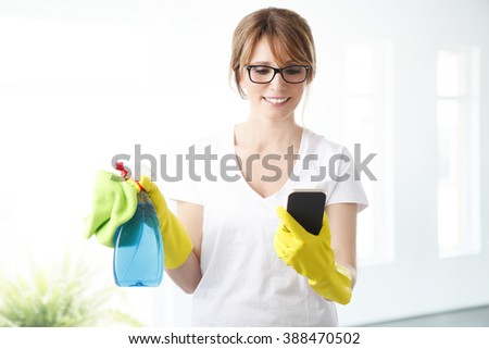 Portrait of middle age woman using her mobile phone and taking a break while cleaning your house. - stock photo