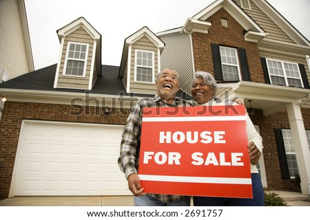 Portrait of middle-aged African-American couple outside house with for sale sign. - stock photo