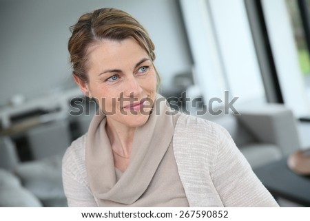 Portrait of middle-aged blond woman at home - stock photo