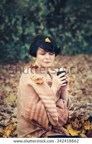 Portrait of middle aged caucasian brunette woman with leaves in her short bob hair, yellow woolen scarf,  sitting on ground outside in park drinking coffee, her eyes closed, cozy autumn fall mood - stock photo