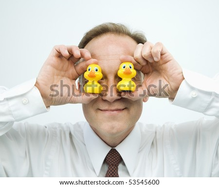 Portrait of middle aged  Caucasian businessman holding rubber ducks up to face. - stock photo