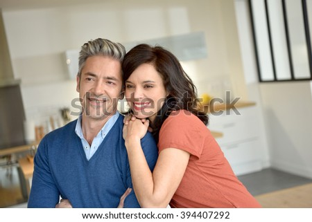 Portrait of middle-aged couple enjoying new home