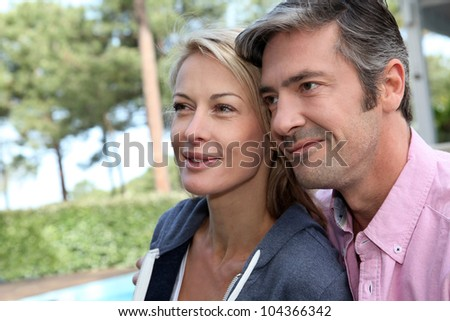 Portrait of middle aged couple sitting outside the house - stock photo
