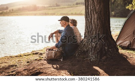 Portrait of middle aged couple sitting under a tree near the lake. Mature couple relaxing at their campsite. - stock photo