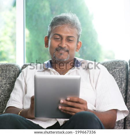 Portrait of middle aged Indian man reading on digital tablet computer and smiling at home. - stock photo