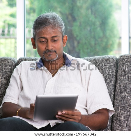 Portrait of middle aged Indian man reading on digital tablet computer at home. - stock photo