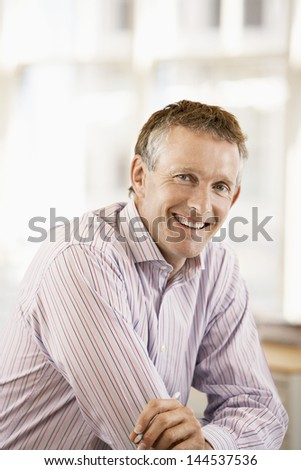 Portrait of middle aged male executive smiling in office - stock photo