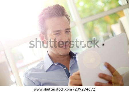 Portrait of middle-aged man at home using tablet - stock photo