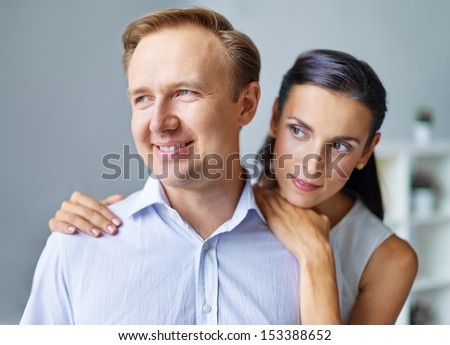 Portrait of middle aged man being embraced by his wife - stock photo