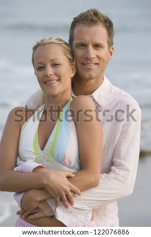 Portrait of middle aged man embracing woman from behind at beach