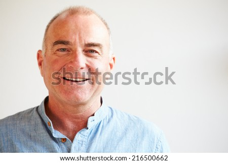 Portrait Of Middle Aged Man Standing By Wall