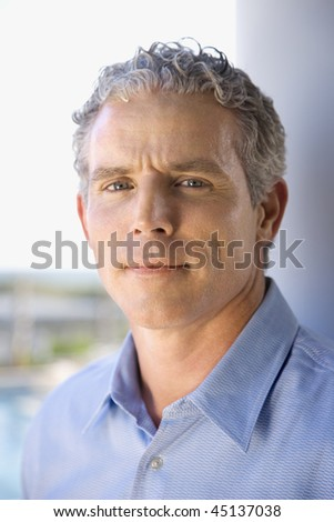 Portrait of middle aged man standing with his back to a column. Vertical shot. - stock photo