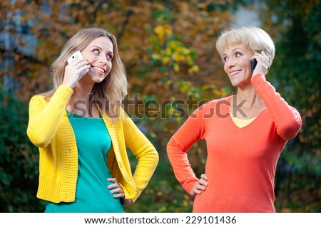 Portrait of middle aged Pretty mother wearing orange pullover and her adult daughter wearing yellow jacket talking on phones smiling to each other outdoors - stock photo