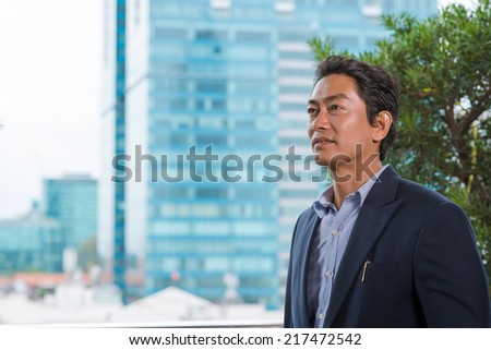 Portrait of middle-aged Vietnamese manager looking aside - stock photo