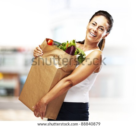 portrait of middle aged woman holding the purchase at a crowded place - stock photo