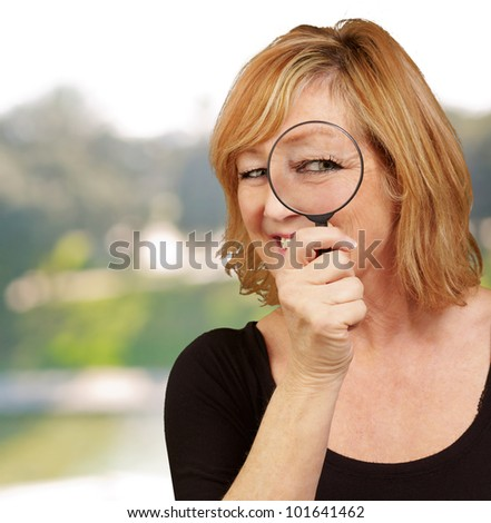 portrait of middle aged woman looking through a magnifying glass - stock photo