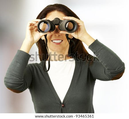 portrait of middle aged woman looking with binoculars indoor