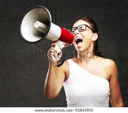 portrait of middle aged woman shouting using megaphone against a grunge wall - stock photo