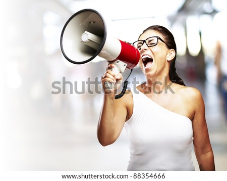portrait of middle aged woman shouting with megaphone in a crowded place - stock photo