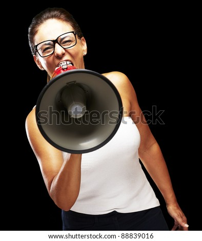 portrait of middle aged woman shouting with megaphone over black background