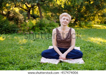 Portrait of middle aged woman smiling on the nature background