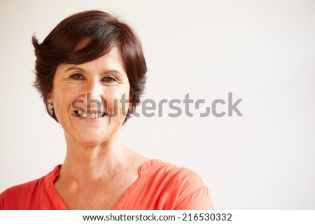 Portrait Of Middle Aged Woman Standing By Wall - stock photo