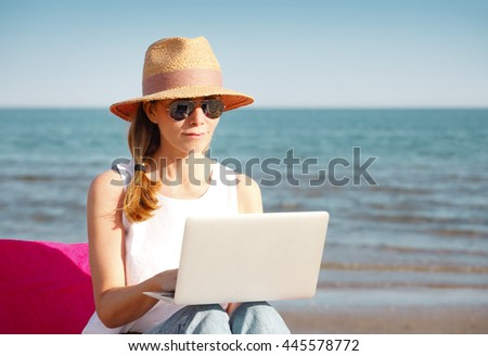 Portrait of middle aged woman using her laptop while sitting on sunbed on the seaside.