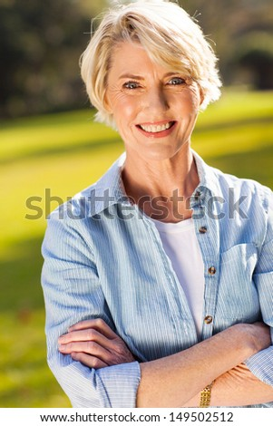 portrait of middle aged woman with arms crossed outdoors - stock photo