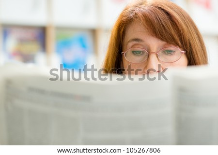 Portrait of middle aged woman with eyeglasses reading paper in library