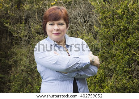 Portrait of middle aged woman with haircut outdoors in spring - stock photo