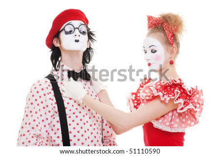 portrait of mimes. woman correcting mans tie. isolated on white