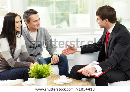 Portrait of modern couple listening to manager explanation about conditions of mortgage - stock photo