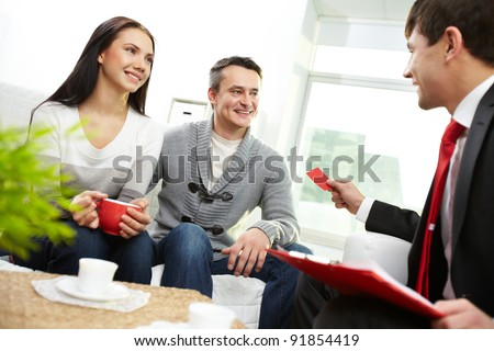 Portrait of modern couple looking at real estate agent giving his visiting card