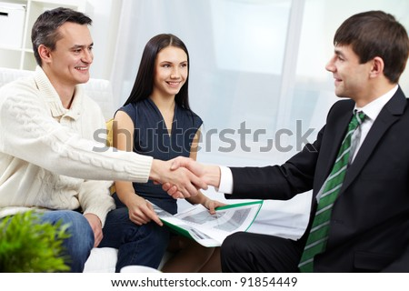 Portrait of modern couple making a deal with real estate manager - stock photo
