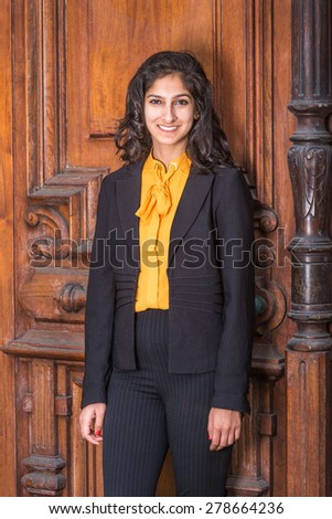 Portrait of Modern East Indian American Lady. Wearing black blazer, orange under shirt, a beautiful business woman with long curly hair standing by vintage style office door way, warmly greeting you. - stock photo