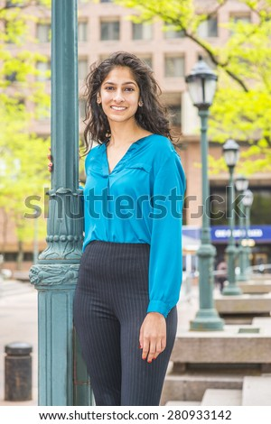Portrait of Modern East Indian American Lady. Wearing long sleeve, V neck shirt, a beautiful college student with long curly hair standing by light pole on school campus, smiling, warmly greeting you. - stock photo