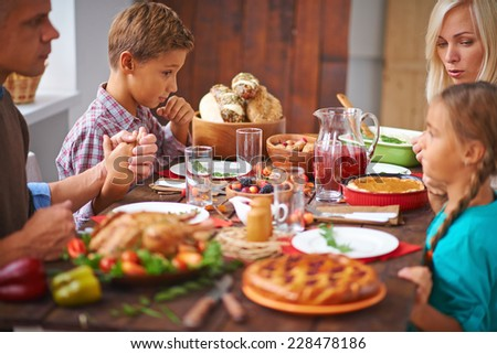 Portrait of modern family praying before festive dinner - stock photo