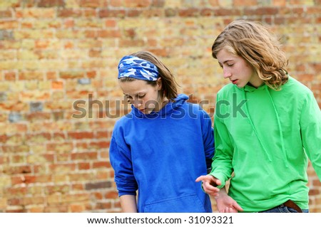 portrait of modern teenagers against brick wall - stock photo