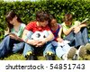 Portrait of modern teens in casual clothes sitting on green grass and writing in copybooks - stock photo