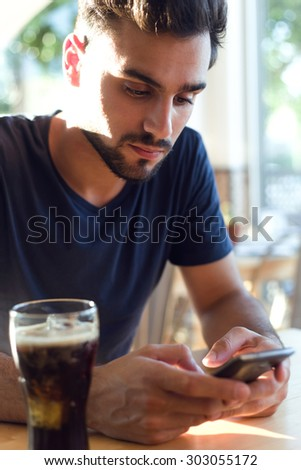 Portrait of modern young man with mobile phone in cafe. - stock photo